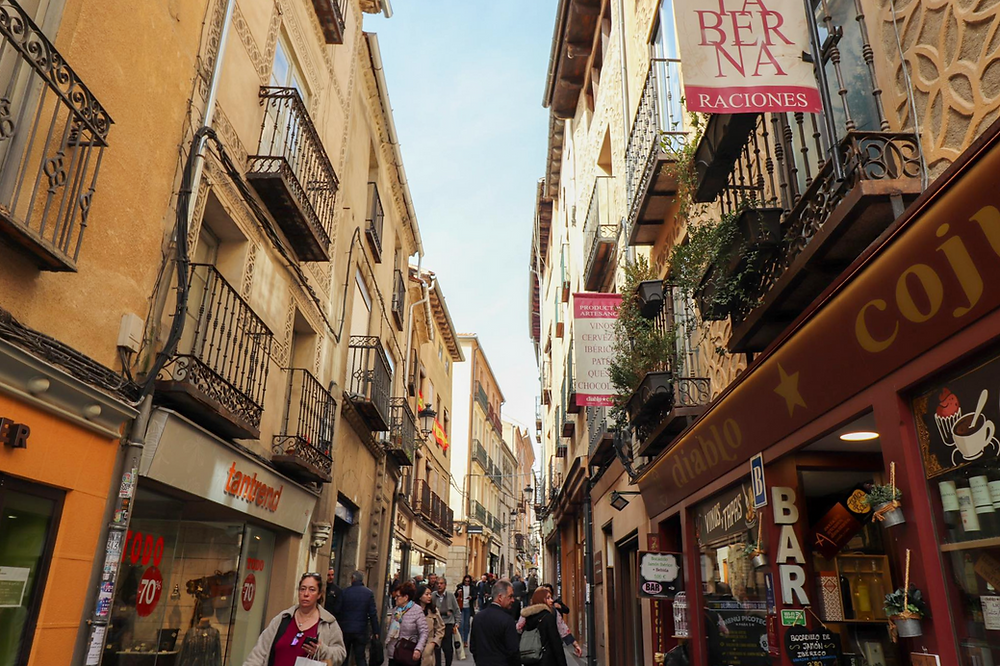 Medieval street in Segovia lined with shops and cafes with people walking.