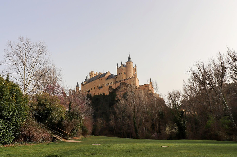 View of the medieval castle that inspired Disney high up on a rock with trees below it and a green field.
