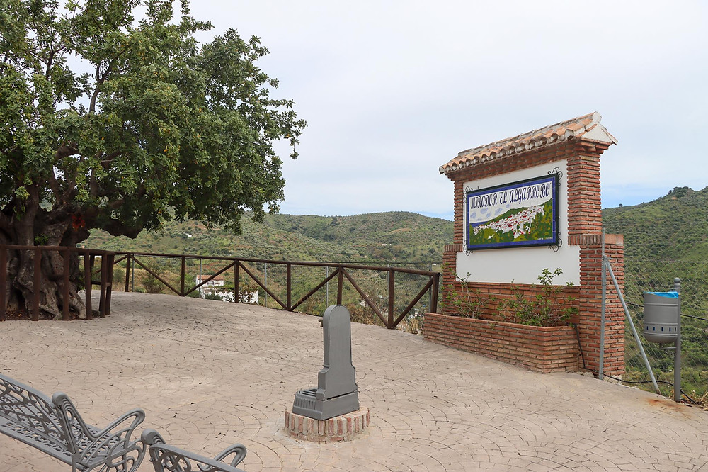 Seating area at a viewpoint overlooking hills with vineyards, a tiled sign in the centre.