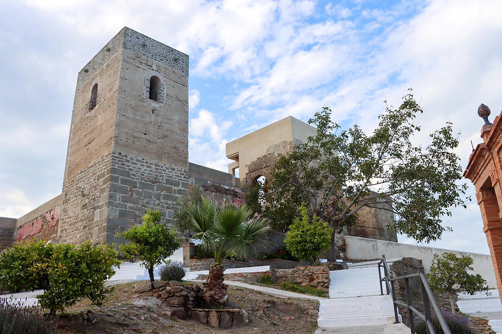 Single castle tower against a blue and cloudy sky with white steps leading up to it and a green leafed tree in front.