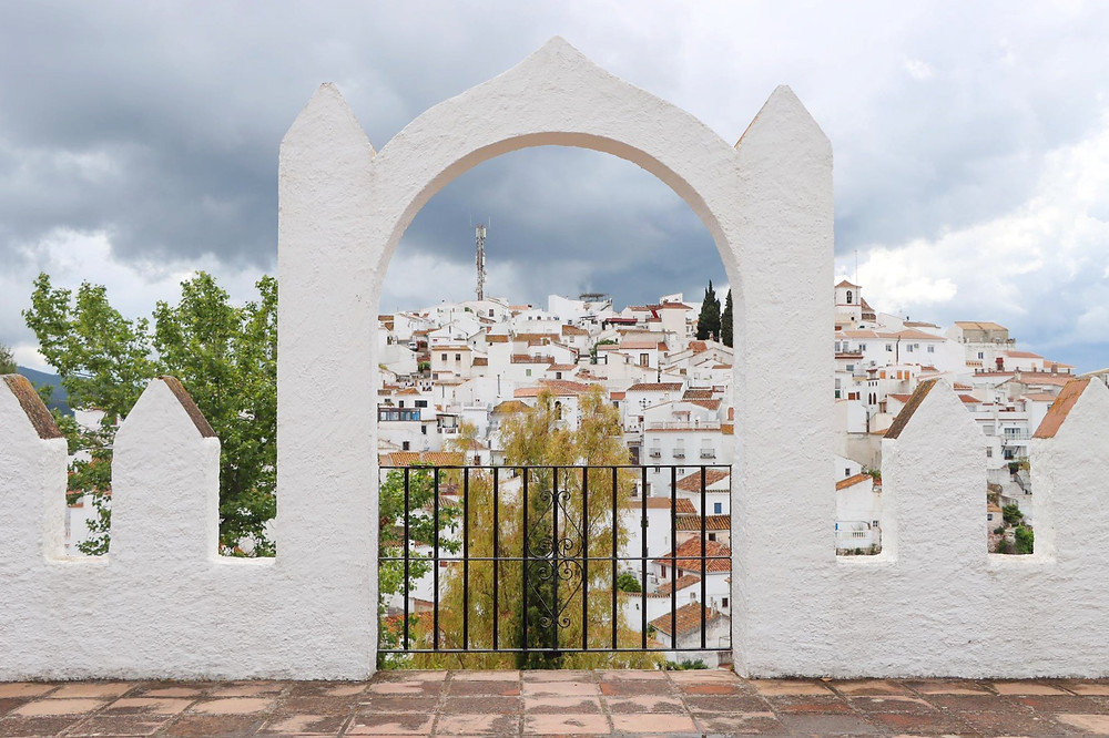 View of a white village seen through a small white arch on a viewpoint on a dark and cloudy day.
