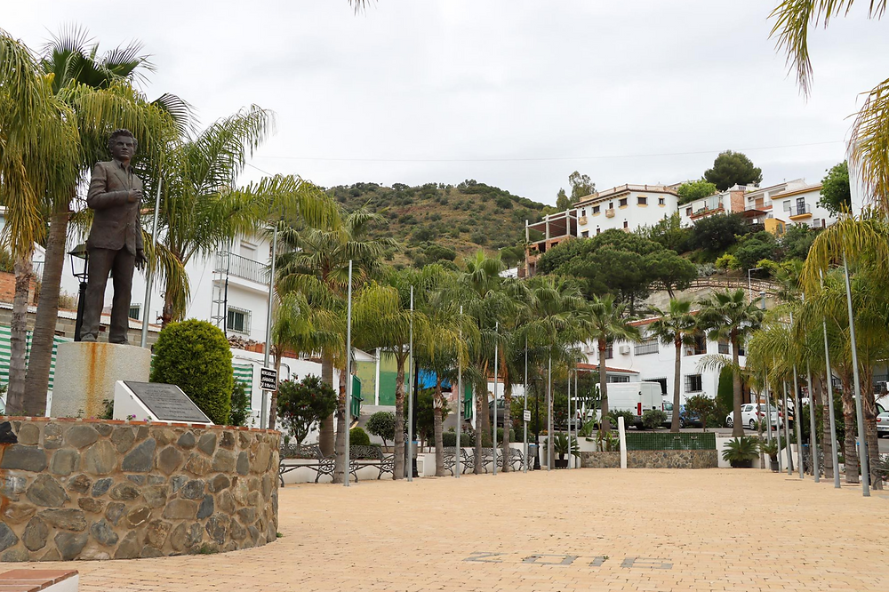 Small empty plaza with a statue at the front lined with palm trees and white houses in the background on a hill.