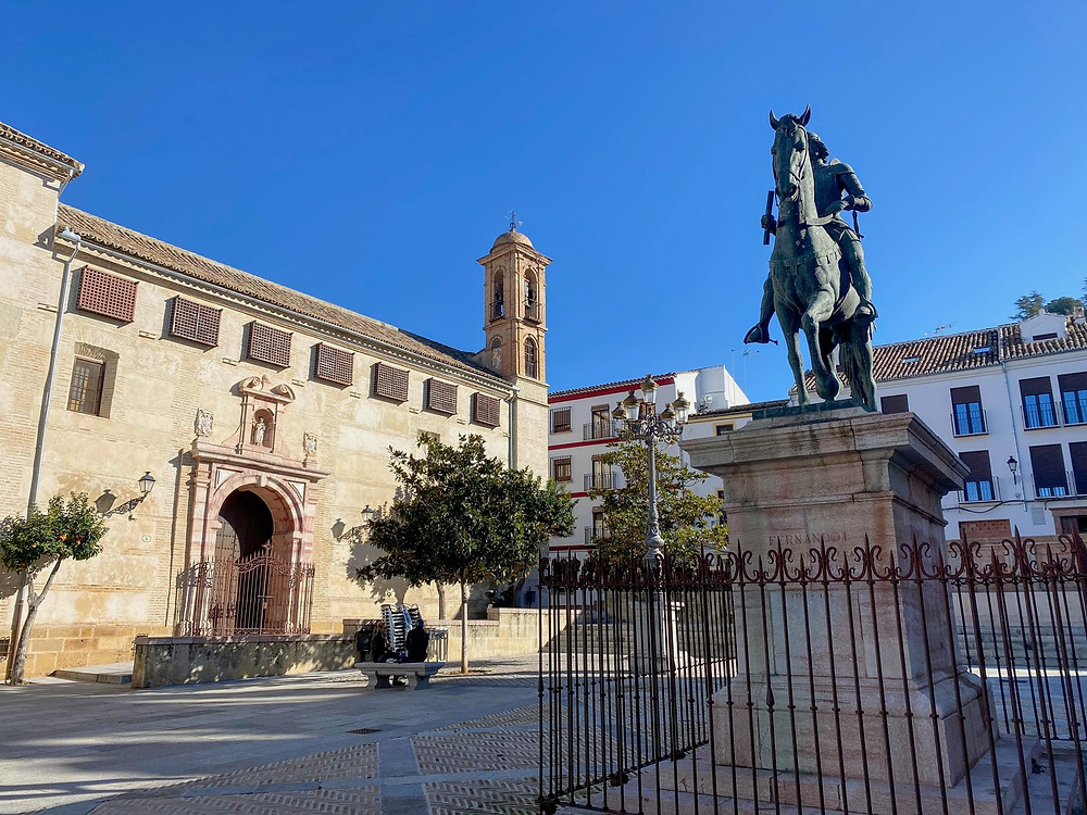 Plaza Coso Viejo with a medieval building on one side and a statue of a man on a horse in the centre in Antequera.