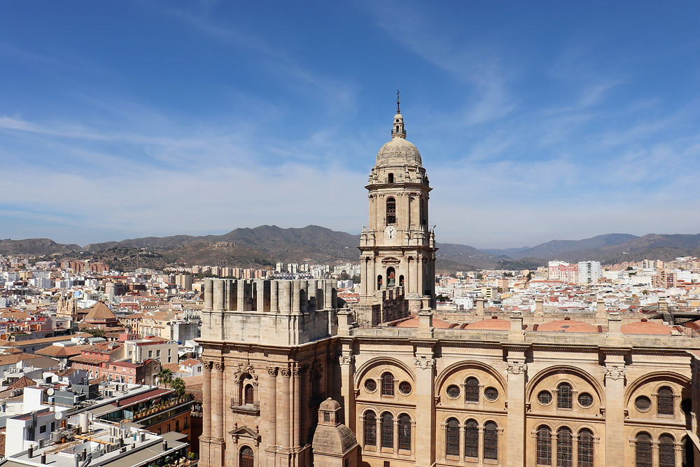View of the cathedral with one tower and an unfinished second tower from the same level, the city and mountains are in the background.