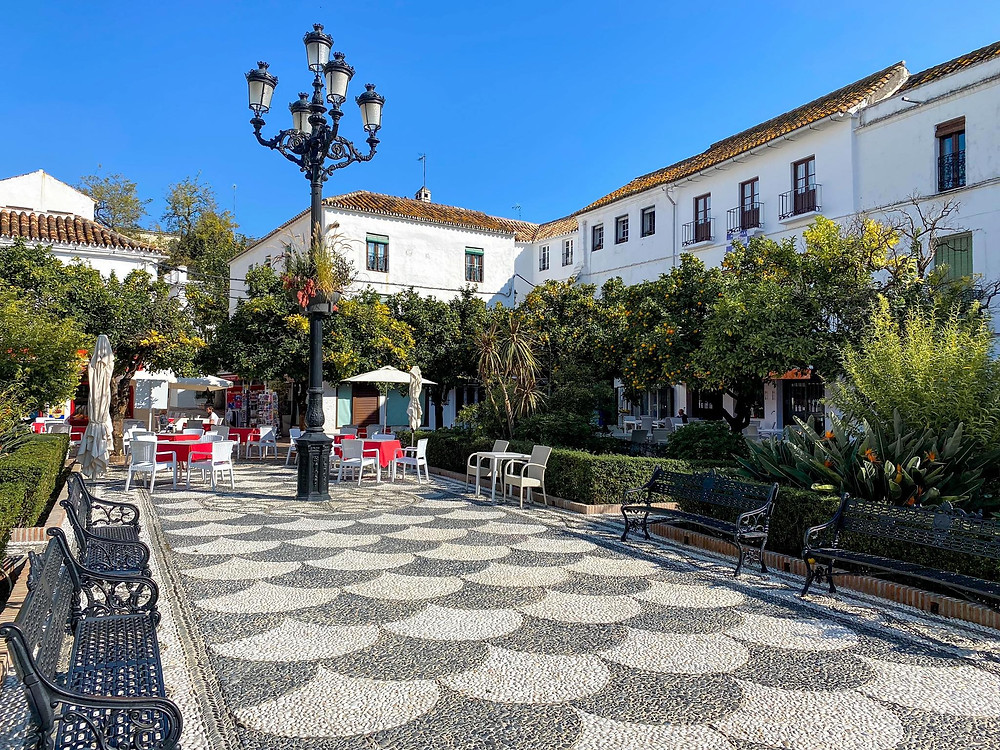 Plaza de los Naranjos or the Orange Square in Marbella's old town. A small square lined with orange trees, benches, and stone pattern ground.