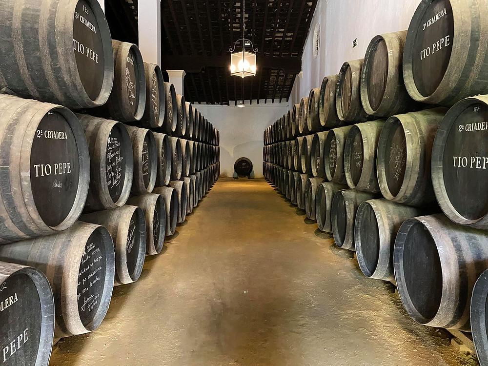 Bodegas Tío Pepe wine barrels stacked inside, Jerez, Cadiz, Spain
