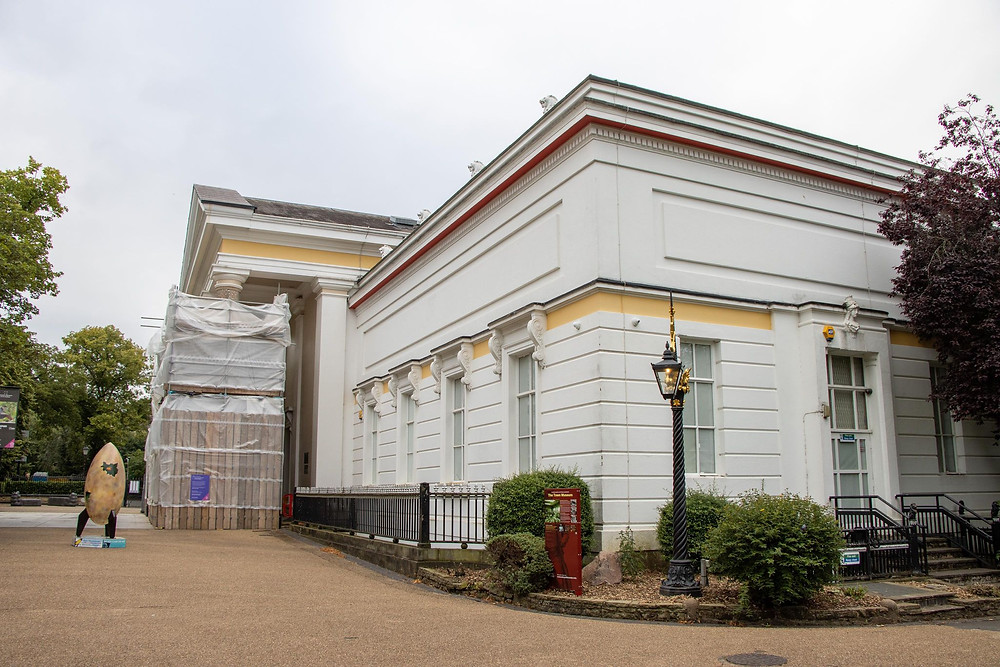 White building with pillars in front, yellow painted trim, and a golden rocket outside of it.