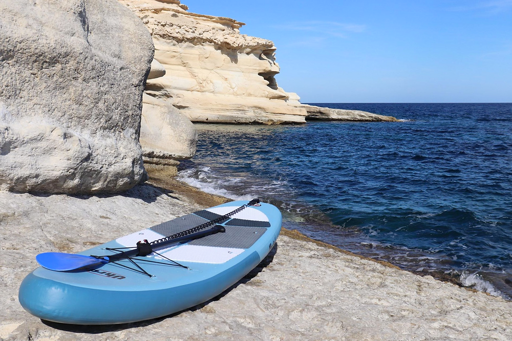 Uhrdal blue paddleboard with oar sitting on the rocks next to the water at Playa el Playazo in Almeria, Spain