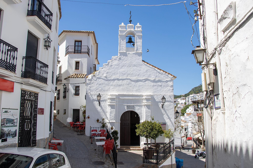 Small white church with a bell tower in the middle surrounded by white houses in a narrow street.