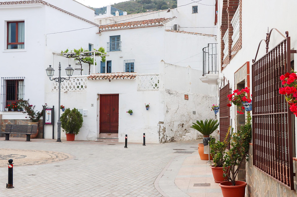 Small plaza in the village with white buildings around it and red flowers on the wall.