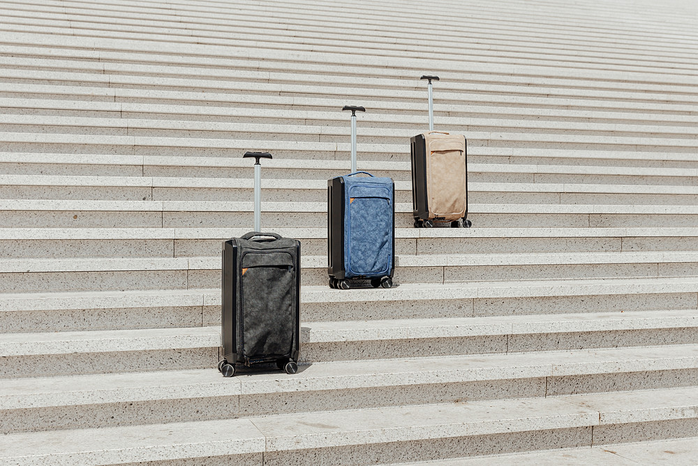 3 foldable suitcases in black, blue, and beige sitting on different levels on outdoor stairs
