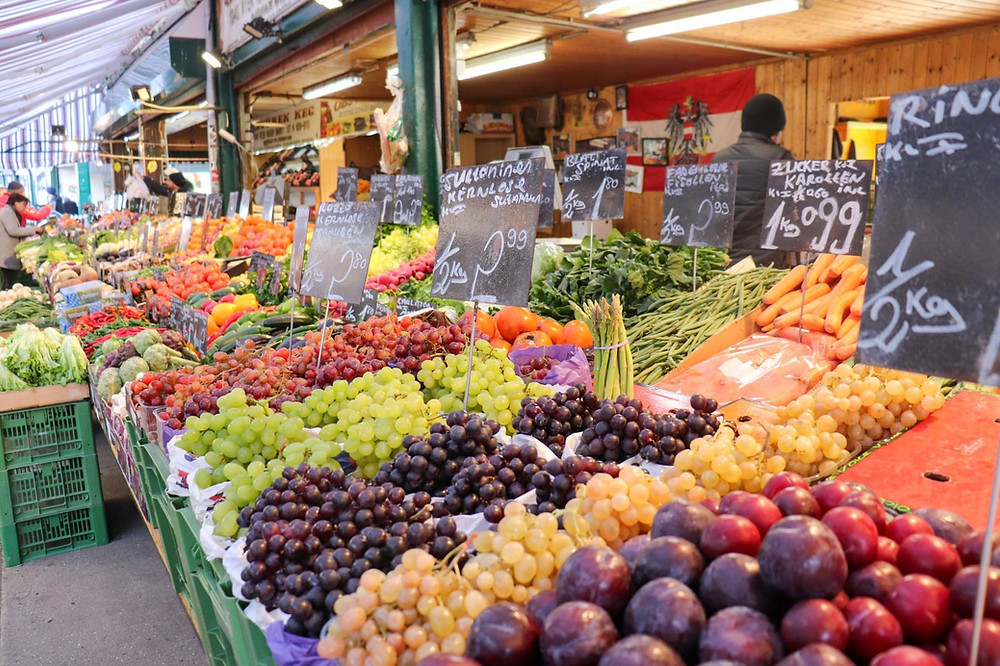 Selection of colourful fruits and vegetables on a long stall inside the market.
