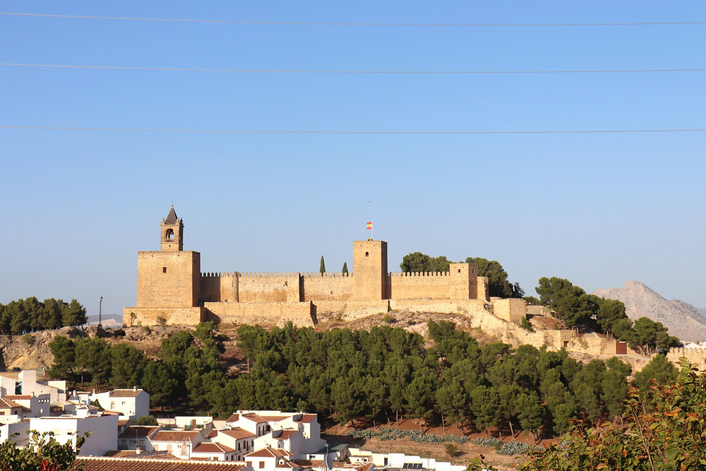 Alcazaba de Antequera from a distance sitting on the top of a hill in Antequera, Spain