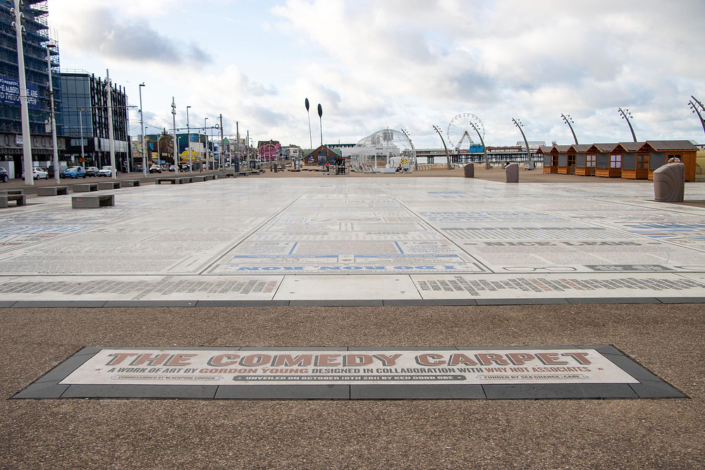 View of a tiled carpet in front of Blackpool Tower along the waterfront with names of comedians on it.