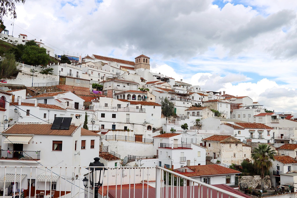 View of a white village slanted on a hillside, with a church tower poking through at the top.