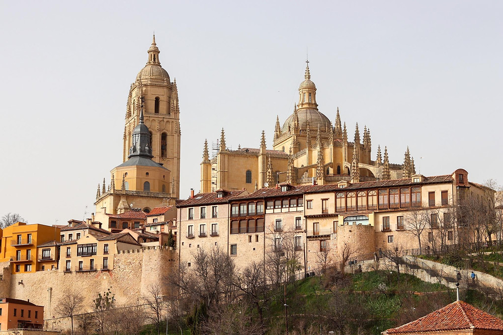 View of Segovia with the cathedral towers rising up in the background over the the roofs of the smaller buildings.
