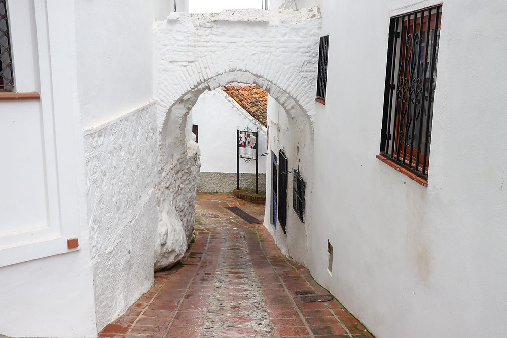 Small Arab arch painted in white connecting two whitewashed buildings in a narrow street.