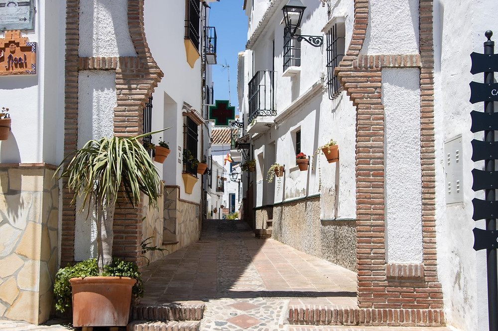 Narrow whitewashed street beginning with a bricked Arab arch.