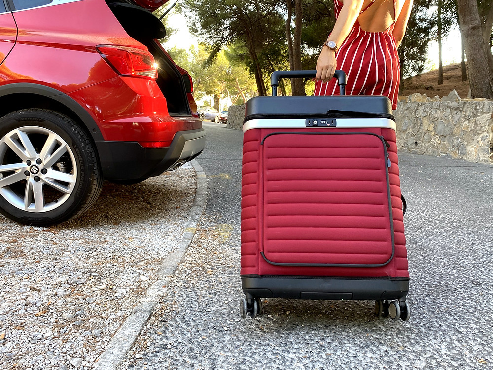 Red Pull Up Suitcase next to red car being pulled on two wheels in Malaga, Spain