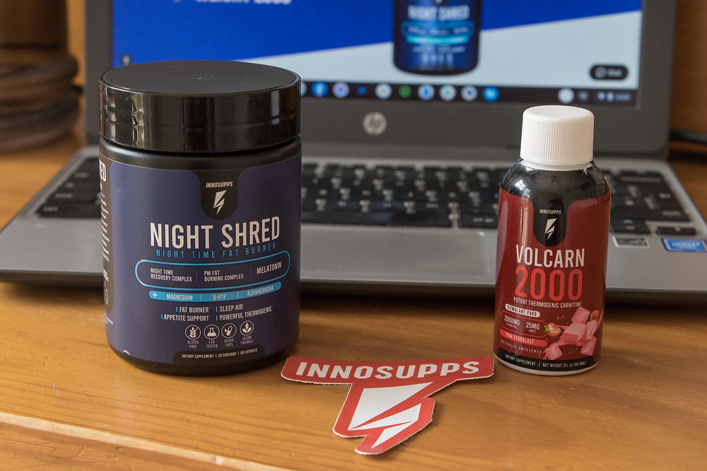 Bottle of pill supplements in a navy packaging, smaller bottle of liquid supplement in a red bottle with a laptop behind them.