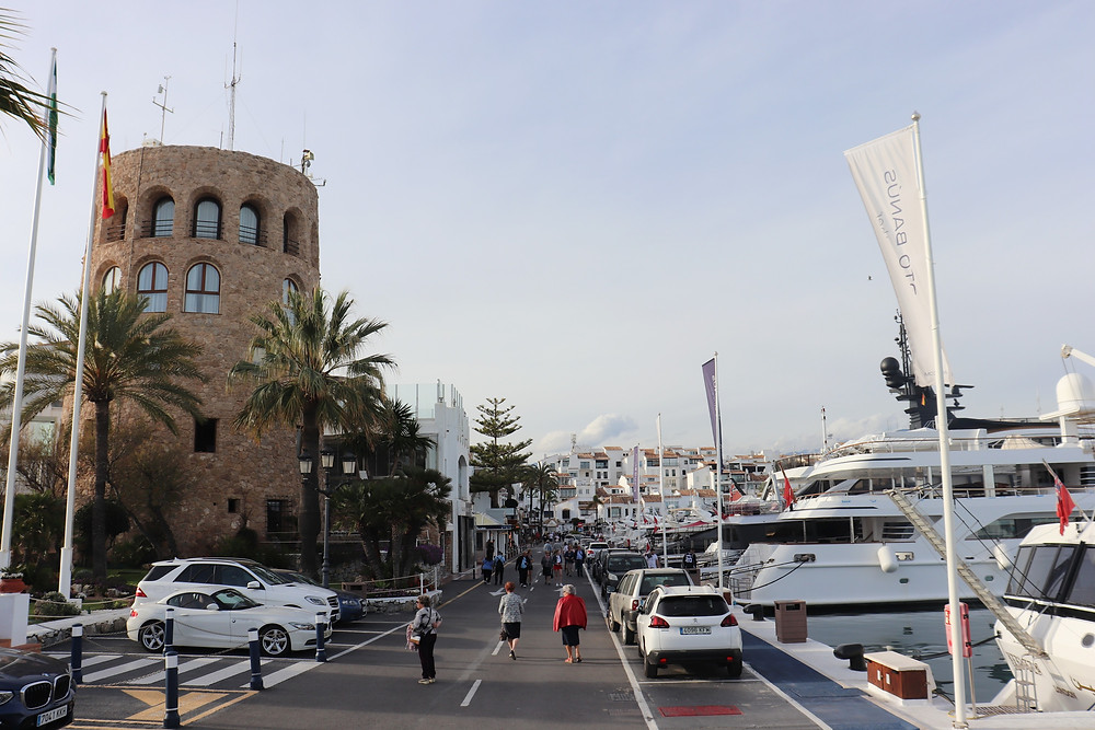 Yachts docked in a marina on the right and an old watch tower on the left hand side.