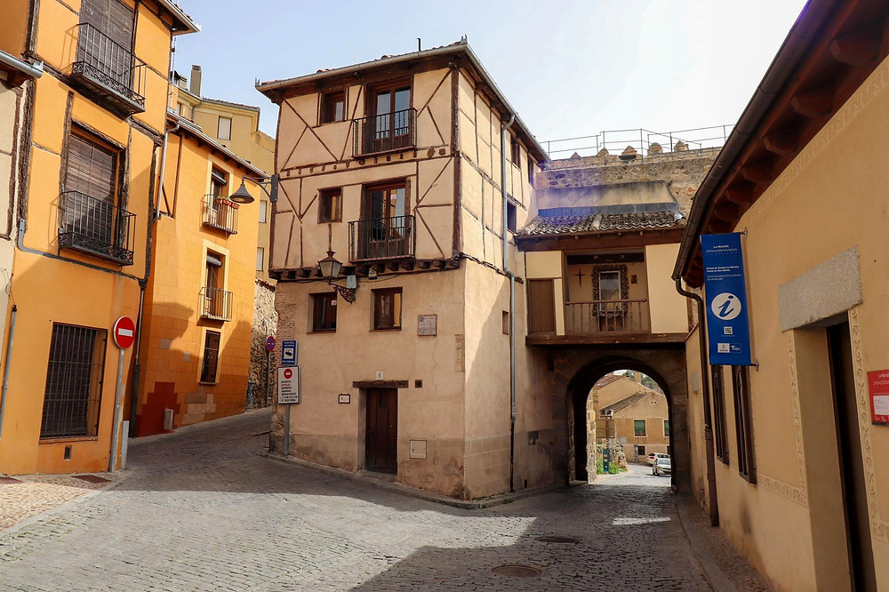 Other side of the large city gate that looks like a medieval house with a balcony over the gate part.