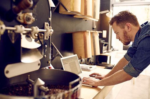 Kávépörkölő mester a laptopján beállítja a frissen megrendelésre pörkölt szemes kávé optimális kávépörkölési profilját - Frissen pörkölt szemeskávé rendelés - Kézműves kávépörkölő