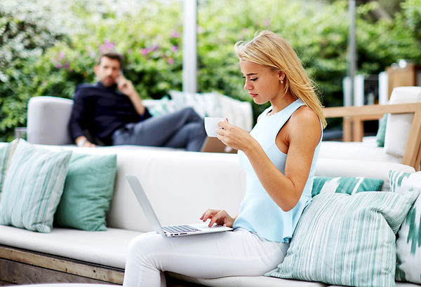 Egy fiatal szőke hölgy egy csésze kávét iszik, miközben az ölében egy laptopon a frissen pörkölt szemes kávé rendelését készíti össze - Frissen pörkölt szemes kávé rendelés
