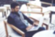 Online Frissen pörkölt szemeskávé rendelést leadó, elegáns és céltudatos férfi, laptoppal az ölében