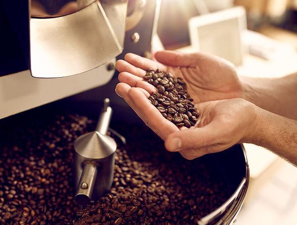 A kávépörkölő mester a tenyerében tartja a frissen pörkölt szemes kávékat. A háttérben egy kávépörkölő gép látható - Frissen pörkölt szemes kávé rendelés