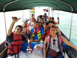 San Blas Day tour guests sitting in panga boat and waving at camera