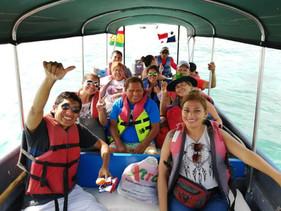 San Blas Day tour guests sitting in panga boat and waving at camera