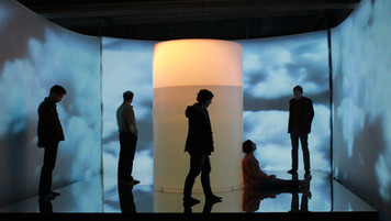 """Deep Circularity; single channel video, rear-projection screens,16' x 16' x 12"""" mirrored platform, inner tubes, 700 gallon water tank, incandescent clamp-light; Art Spin, Toronto"""