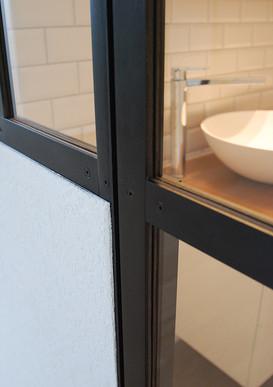 Verrière pour douche et salle de bain en inox avec fausse patine noir.  Architectes : Voumard et Mercier Photo : Voumard et Mercier