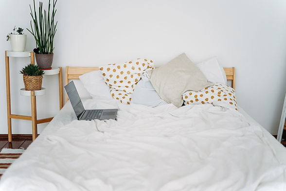 opened-laptop-notebook-on-bed-at-bright-