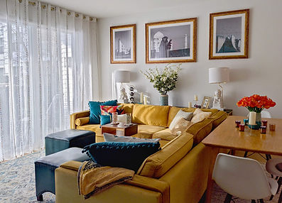 living room with mustard velvet sectional, photographs of india, pillows and antique foo dog statues
