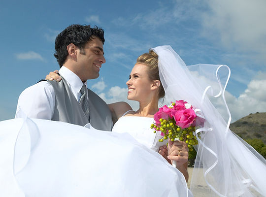 Handsome groom holds in hands his aristocratic blonde bride  | Paphos Town Hall pics photographer