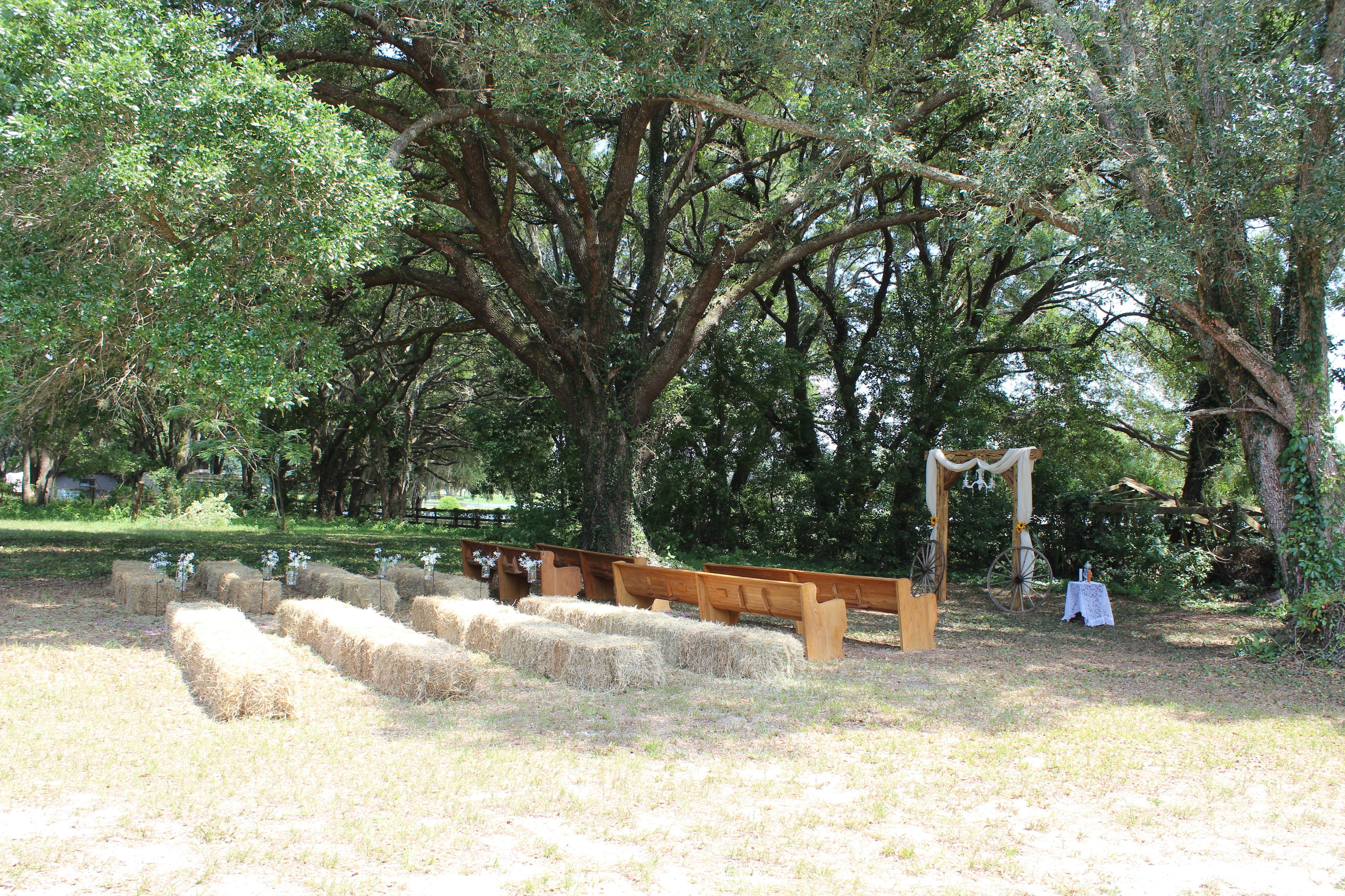 Ceremony pews hay bales arch.jpg