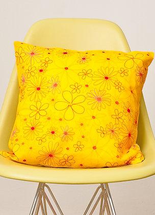Gelbes Kissen mit bunter Alloverblüte