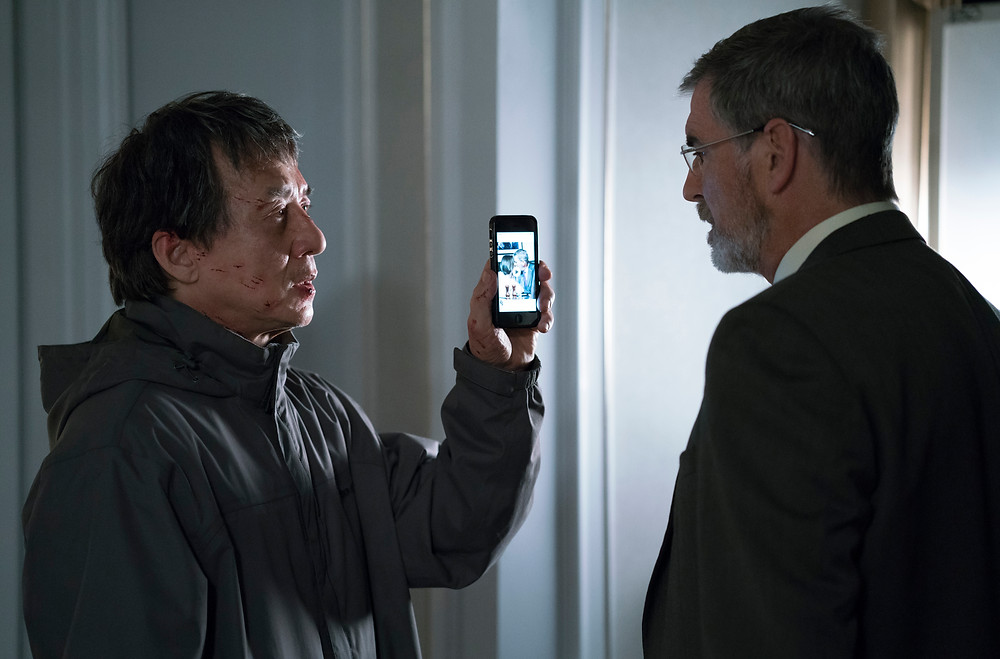 (Left to Right) Jackie Chan as Quan and Pierce Brosnan as Hennessy in hotel suite in THE FOREIGNER - Motion Picture Artwork © 2017 STX Financing, LLC. All Rights Reserved.
