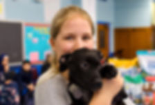 Muttigrees student holding a puppy and smiling.
