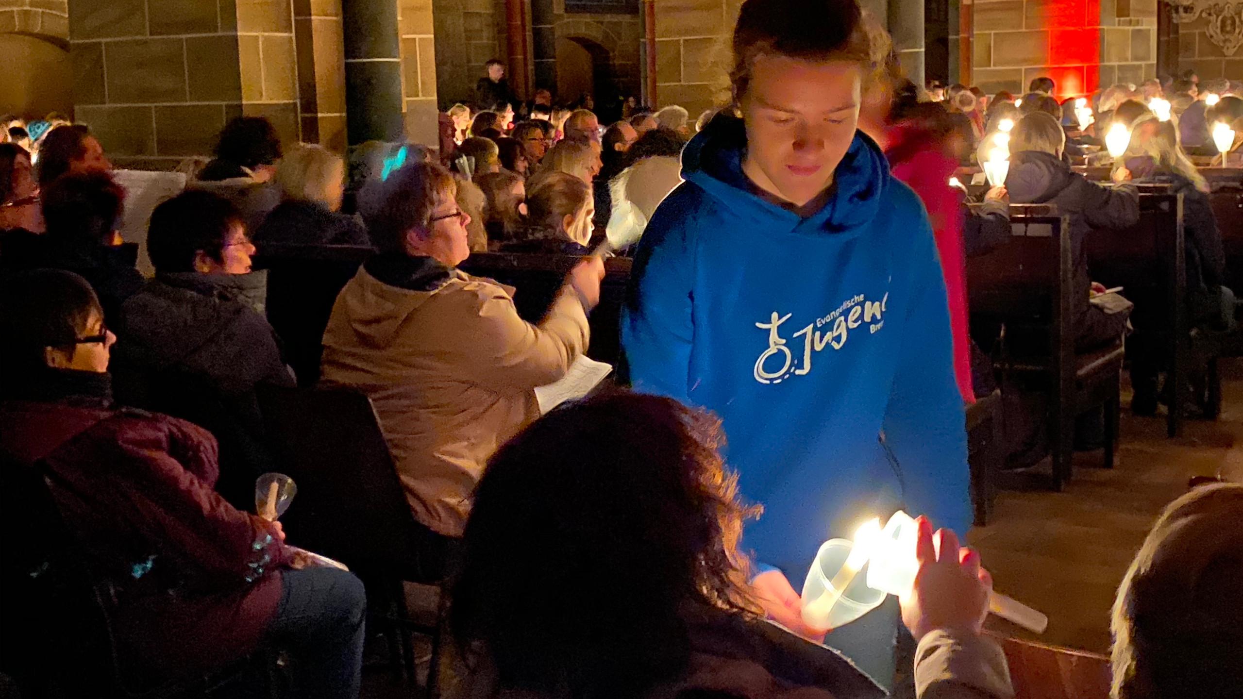 Nahaufnahme davon wie jemand mit der Kerze rumgeht und die Kerzen der Gäste anzündet.