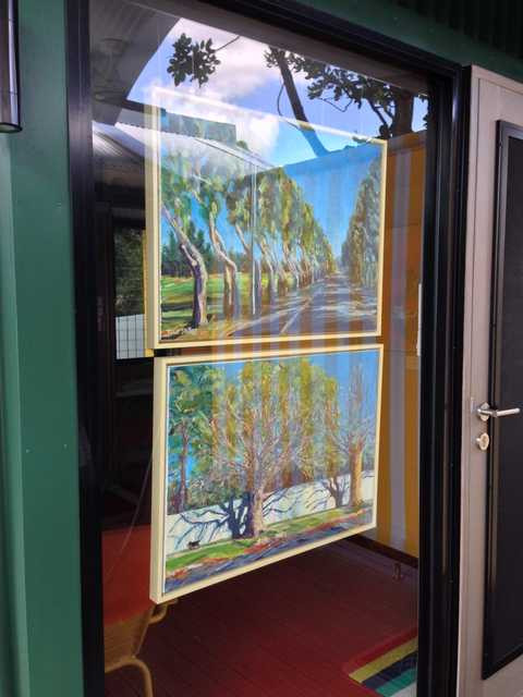Painted trees in the window reflecting real trees beside the gallery