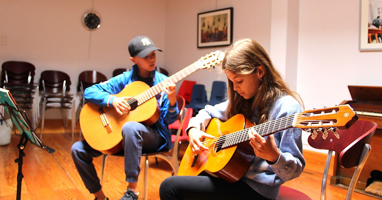 brother and sister learning guitar together