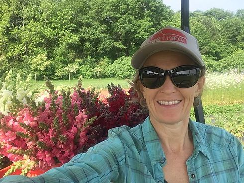 Photo of farmer and owner, Suzanne Nolter, in front of a cut flower farm field.