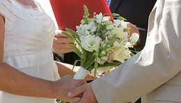 A bridal bouquet of local flowers and a couple holding hands at a wedding ceremony. White and green flowers include hydrangea, snapdragons and grasses.