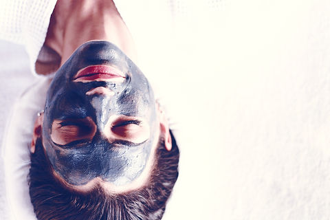 Woman relaxing with a charcoal facial ma
