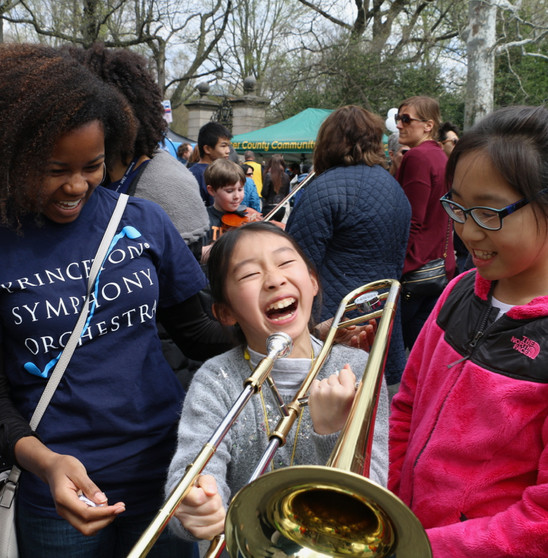 A Communiversity attendee tries out the trombone with the help of a PSO volunteer staffer.