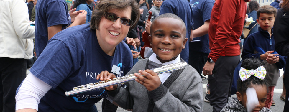 A Communiversity attendee poses for a photo with PSO staffer Suzanne Wray after trying out the flute.