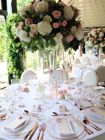 Tall vase wedding table centre with rose gold accents.